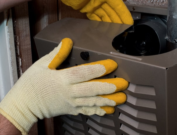 A technician replaces a furnace grill for a Greenwood homeowner