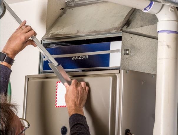 A technician removes a furnace panel for a Zionsville HVAC inspection