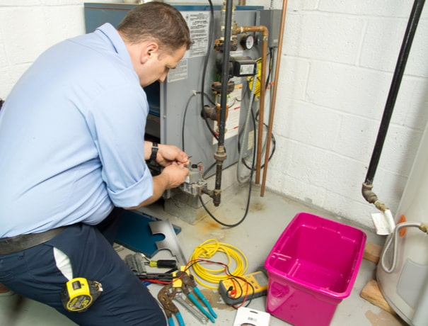 A technician repairs a gas furnace in a Plainfield home